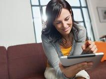 Mujer que usa la PC de la tablilla Imagen de archivo