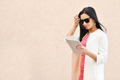 Mujer que usa la PC de la tablilla al aire libre Foto de archivo