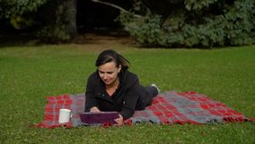 Mujer que usa la PC de la tableta en el parque almacen de video