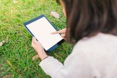 Mujer que usa la PC digital de la tablilla en el parque foto de archivo libre de regalías