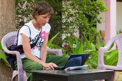 Mujer que usa la PC en vacaciones fotos de archivo libres de regalías