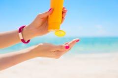 Mujer que usa la protección solar en la playa fotografía de archivo