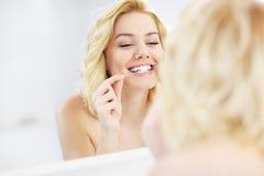 Mujer que usa la seda dental Foto de archivo libre de regalías