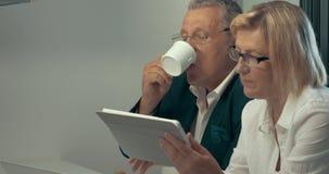 Mujer que usa la tableta, café de consumición del hombre almacen de metraje de vídeo