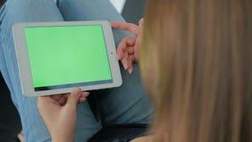 Mujer que usa la tableta con la pantalla verde almacen de video