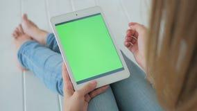 Mujer que usa la tableta con la pantalla verde metrajes