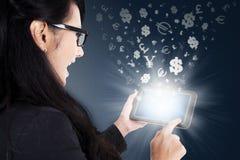Mujer que usa la tableta con símbolos de moneda Imágenes de archivo libres de regalías
