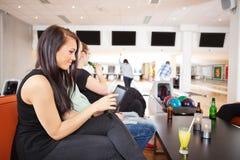Mujer que usa la tableta de Digitaces con los amigos que ruedan adentro Foto de archivo