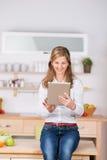 Mujer que usa la tableta de Digitaces en cocina Imagenes de archivo