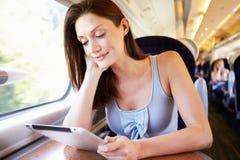 Mujer que usa la tableta de Digitaces en el tren Imágenes de archivo libres de regalías