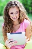 Mujer que usa la tableta digital al aire libre Foto de archivo libre de regalías