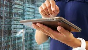 Mujer que usa la tableta digital contra códigos binarios almacen de metraje de vídeo