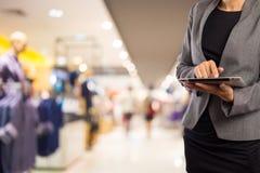 Mujer que usa la tableta en alameda de compras Imagen de archivo