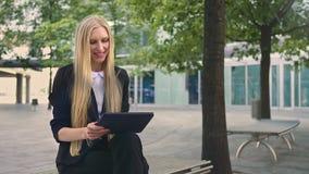 Mujer que usa la tableta en banco Mujer de negocios formal que se sienta en banco en patio de la oficina y la tableta de la ojead almacen de video
