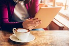 Mujer que usa la tableta en cafetería Foto de archivo libre de regalías