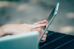 Mujer que usa la tableta en el parque Imagen de archivo libre de regalías