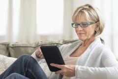 Mujer que usa la tableta en el sofá Fotografía de archivo libre de regalías