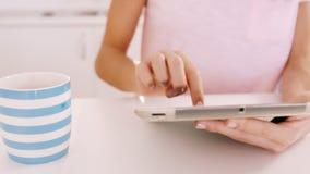 Mujer que usa la tableta en una tabla almacen de metraje de vídeo