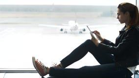 Mujer que usa la tableta moderna a disposición y sentándose en termina del aeropuerto almacen de video
