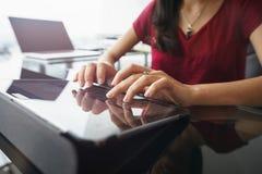 Mujer que usa la tableta para el trabajo diario en oficina Foto de archivo