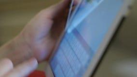 Mujer que usa la tableta para en la línea compra con la tarjeta de crédito almacen de metraje de vídeo