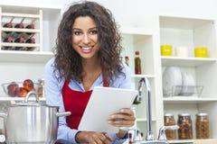 Mujer que usa la tableta que cocina en cocina Imagenes de archivo