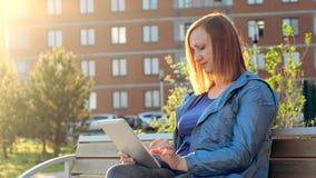Mujer que usa la tableta que se sienta en banco en ciudad metrajes