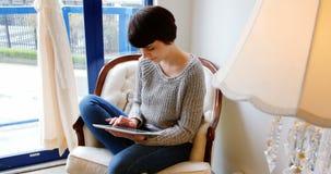 Mujer que usa la tablilla digital metrajes