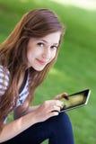 Mujer que usa la tablilla digital al aire libre Imágenes de archivo libres de regalías