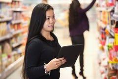 Mujer que usa la tablilla digital en centro comercial foto de archivo