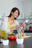 Mujer que usa la tablilla en cocina Fotos de archivo libres de regalías