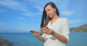 Mujer que usa la tarjeta de crédito el las vacaciones que hacen compras en línea con el teléfono móvil en el fondo azul claro del metrajes