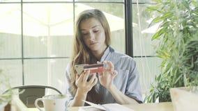 Mujer que usa la tarjeta de crédito que hace compras en línea con smartphone en café almacen de video