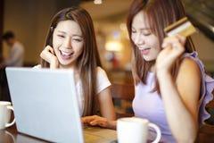 Mujer que usa la tarjeta de crédito y el ordenador portátil para las compras en línea Imagenes de archivo