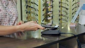 Mujer que usa la tecnología de NFC para el pago en la tienda almacen de metraje de vídeo