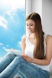 Mujer que usa la ventana de la tableta, chica joven que lee la almohadilla táctil blanca Imagen de archivo libre de regalías