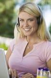 Mujer que usa las auriculares que llevan del ordenador portátil Foto de archivo libre de regalías