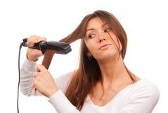 Mujer que usa a las enderezadoras del pelo para el peinado Fotografía de archivo libre de regalías