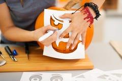 Mujer que usa las plantillas para tallar la Jack-O-linterna de la calabaza primer Imagen de archivo libre de regalías