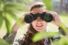 Mujer que usa los prismáticos Imagenes de archivo