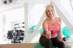 Mujer que usa pesos de la mano en bola suiza en la gimnasia Fotos de archivo