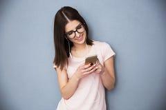 Mujer que usa smartphone con los auriculares Fotografía de archivo libre de regalías