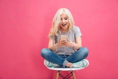 Mujer que usa smartphone con los auriculares Imagen de archivo libre de regalías