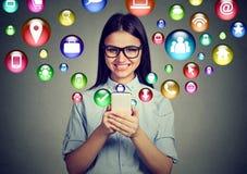 Mujer que usa smartphone con los iconos de los símbolos del uso que vuelan de la pantalla Foto de archivo