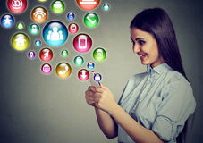 Mujer que usa smartphone con los iconos del uso que vuelan de la pantalla Imagen de archivo libre de regalías