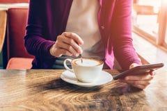 Mujer que usa smartphone en cafetería Imágenes de archivo libres de regalías