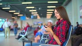 Mujer que usa smartphone en el aeropuerto Muchacha del viajero que espera en aeropuerto y que usa su teléfono elegante Hembra bas almacen de video