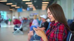 Mujer que usa smartphone en el aeropuerto Muchacha del viajero que espera en aeropuerto y que usa su teléfono elegante Hembra bas metrajes