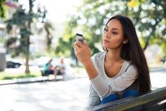 Mujer que usa smartphone en el banco al aire libre Fotos de archivo libres de regalías