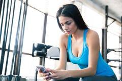 Mujer que usa smartphone en el gimnasio Imagen de archivo
